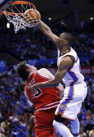 Oklahoma City Thunder guard Russell Westbrook, right, dunks over Chicago Bulls center Omer Asik, left, in the third quarter of an NBA basketball game in Oklahoma City, Sunday, April 1, 2012. (AP Photo/Sue Ogrocki)