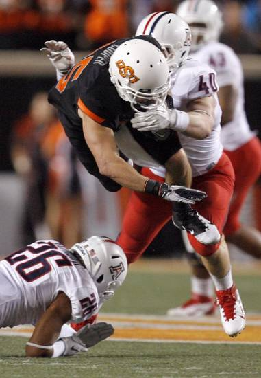 Oklahoma State's Josh Cooper is tackled by Arizona's Derek Earls (40) and Jourdon Grandon (26) during their game Thursday night. PHOTO BY SARAH PHIPPS, The Oklahoman