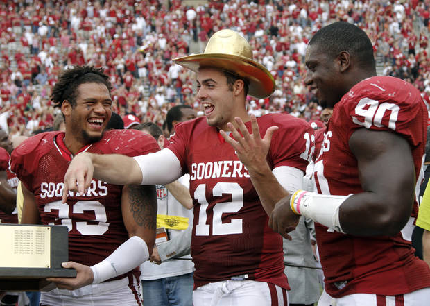 OU's Landry Jones (12) wears the Golden Hat Trophy with teammates OU's Trey Millard (33) and David King (90) during the Red River Rivalry college football game between the University of Oklahoma (OU) and the University of Texas (UT) at the Cotton Bowl in Dallas, Saturday, Oct. 13, 2012. Photo by Chris Landsberger, The Oklahoman