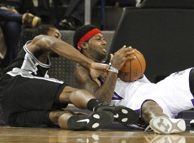 Sacramento Kings forward James Johnson, right, protects the ball from San Antonio Spurs forward Kawhi Leonard during the first quarter of an NBA basketball game in Sacramento, Calif., Friday, Nov. 9, 2012. (AP Photo/Rich Pedroncelli)