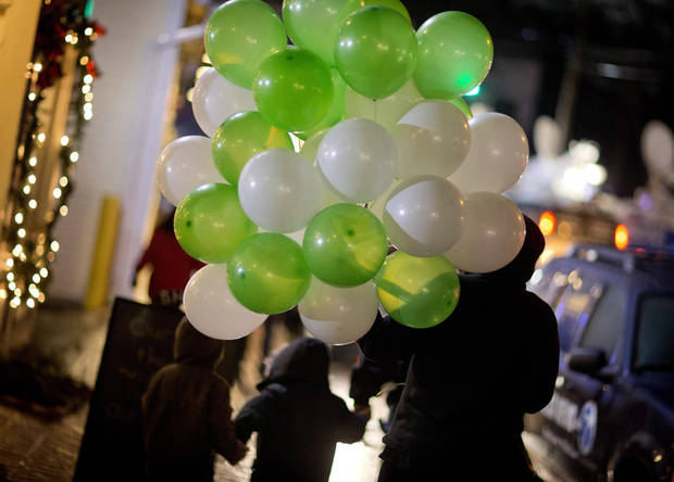 Mourners carry balloons as the walk to a memorial for the victims of the Sandy Hook Elementary School shooting, Monday, Dec. 17, 2012, in Newtown, Conn. (AP Photo/David Goldman) ORG XMIT: CTDG125