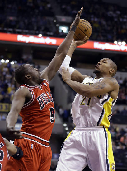 Indiana Pacers forward David West, right, hits a shot over Chicago Bulls forward Luol Deng in the second half of an NBA basketball game in Indianapolis, Monday, Feb. 4, 2013. The Pacers defeated the Bulls 111-101. (AP Photo/Michael Conroy)