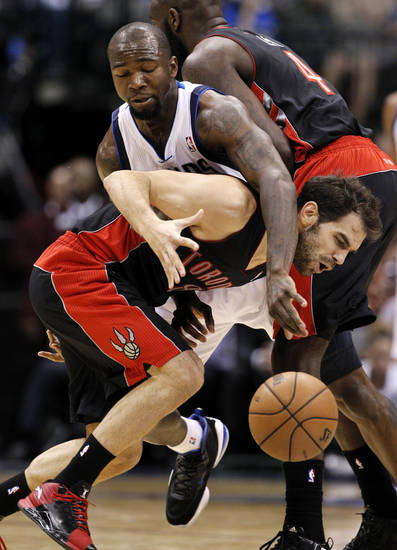 Dallas Mavericks' Dominique Jones wraps up and fouls Toronto Raptors' Jose Calderon (8), of Spain, as Quincy Acy (4) sets up the pick in the second half of an NBA basketball game, Wednesday, Nov. 7, 2012, in Dallas. The Mavericks won 109-104. (AP Photo/Tony Gutierrez)