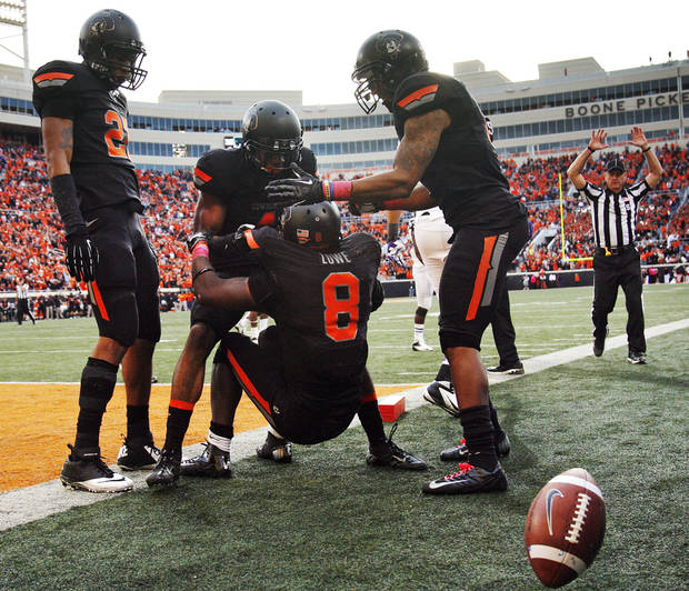 From left, Oklahoma State's Lyndell Johnson (27), Justin Gilbert (4) and Shamiel Gary (7) help Daytawion Lowe (8) up after Lowe returned an interception to the 1-yard line in the fourth quarter during a college football game between Oklahoma State University (OSU) and Texas Christian University (TCU) at Boone Pickens Stadium in Stillwater, Okla., Saturday, Oct. 27, 2012. OSU won, 36-14. Photo by Nate Billings, The Oklahoman