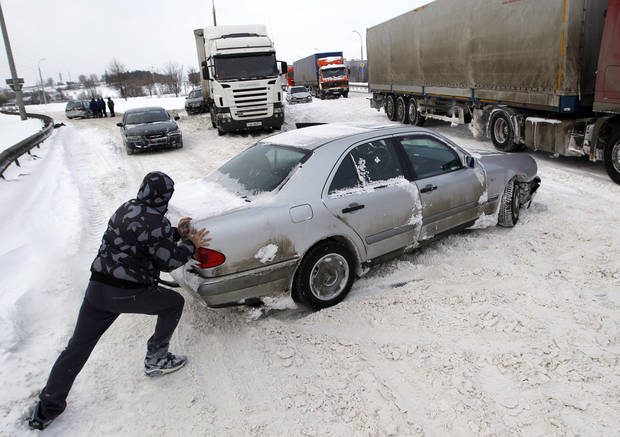 A man pushes a car after a heavy snowstorm in Minsk, Belarus, Saturday, March 16, 2013. Cold and windy weather came to Belarus on Friday. (AP Photo/Sergei Grits)