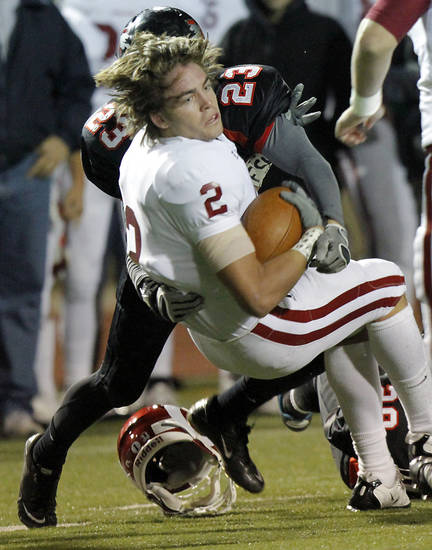 Owasso's Nick DiMarco loses his helmet as he is hit by Westmoore's Addison Staggs during their playoff game at Moore High School in Moore, Oklahoma, on Friday Nov. 19, 2010. Photo by John Clanton, The Oklahoman