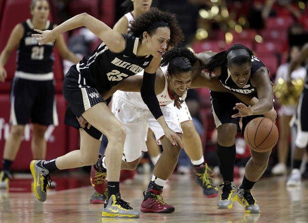 Maryland forward Alyssa Thomas, center, struggles for possession of the ball with Wake Forest forward Dearica Hamby, left, and guard Asia Williams in the first half of an NCAA college basketball game in College Park, Md., Sunday, March 3, 2013. (AP Photo/Patrick Semansky)