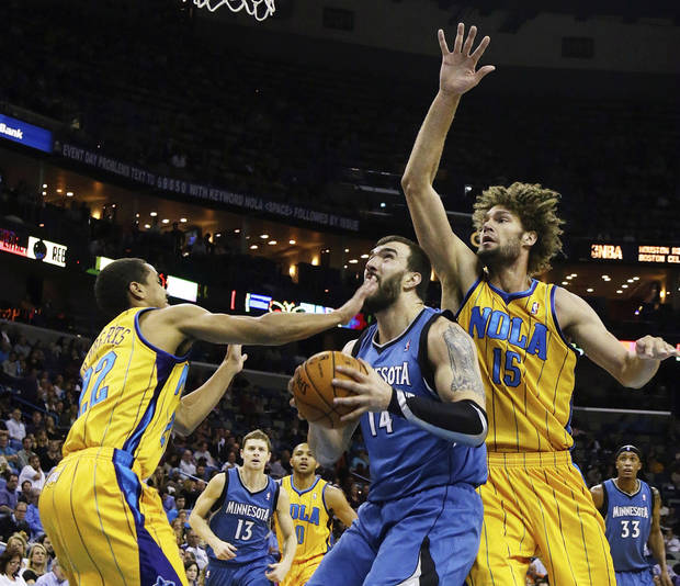 New Orleans Hornets guard Brian Roberts (22) and center Brian Roberts (15) reach in on Minnesota Timberwolves center Nikola Pekovic (14) in the first half of an NBA basketball game in New Orleans, Friday, Jan. 11, 2013. (AP Photo/Bill Haber)