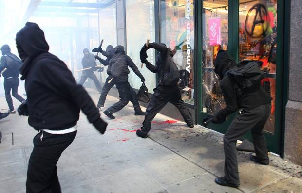 Protesters break windows on downtown businesses including American Apparel and NikeTown during a May Day rally on Tuesday, May 1, 2012 in downtown Seattle. About two dozen of the hundreds of protesters that participated in the march shattered windows and caused mayhem in Seattle. (AP Photo/Seattlepi.com, Joshua Trujillo)
