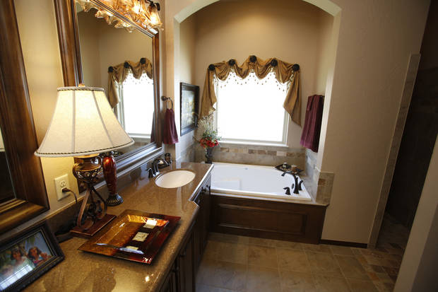 Subdued lighting adds a rich cast to the master bath in a model home by J.W. Mashburn Homes at 3129 SW 136 Terrace. Photo by  Steve Gooch,  The Oklahoman
