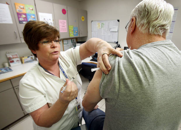 Cleveland County Health Department nurse D.J. Gentry gives a flu shot to George Henschel.  PHOTO BY STEVE SISNEY, THE OKLAHOMAN