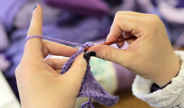 "Aimee Merick crochets a purple cap, for the ""Click for Babies, Period of Purple Crying Caps"" program to raise awareness about normal infant crying and the dangers of shaking a baby. <strong>David McDaniel - The Oklahoman</strong>"