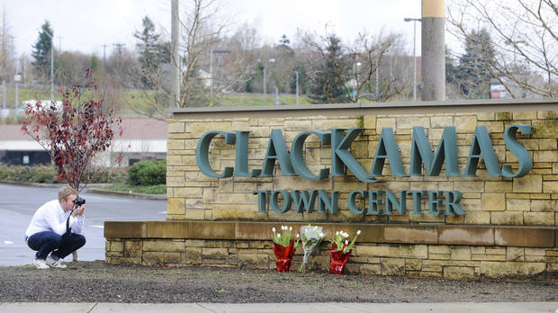 A man photographs flowers placed earlier at an entrance to Clackamas Town Center in Portland, Ore., Wednesday Dec. 12, 2012. The gunman who killed two people and himself in a shooting rampage at the suburban mall Tuesday was 22 years old and used a stolen rifle from someone he knew, authorities said Wednesday. (AP Photo/Greg Wahl-Stephens)  ORG XMIT: ORGW120
