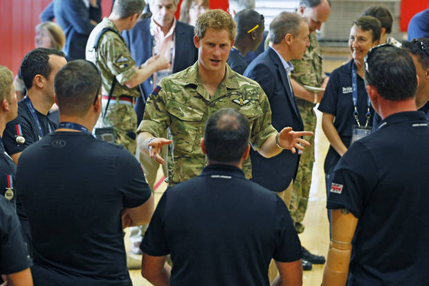 Britain's Prince Harry talks with members of the British Warrior Games Team who relaxed in a gymnasium before the opening of 2013 Warrior Games, at the U.S. Olympic Training Center, in Colorado Springs, Colo., Saturday May 11, 2013. (AP Photo/Brennan Linsley, Pool)