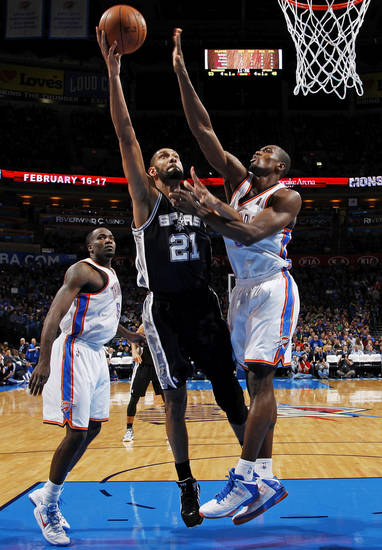 San Antonio's Tim Duncan (21) shoots against Oklahoma City's Serge Ibaka (9) as Kendrick Perkins (5) looks on during an NBA basketball game between the Oklahoma City Thunder and the San Antonio Spurs in Oklahoma City Monday, Dec. 17, 2012. Oklahoma City won, 107-93. Photo by Nate Billings, The Oklahoman