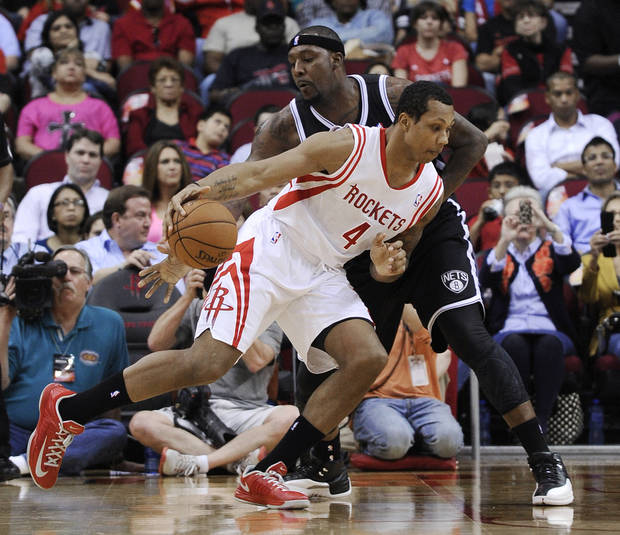 Houston Rockets' Greg Smith (4) drives the ball past Brooklyn Nets' Andray Blatche during the first half of an NBA basketball game Saturday, Jan. 26, 2013, in Houston. (AP Photo/Pat Sullivan)