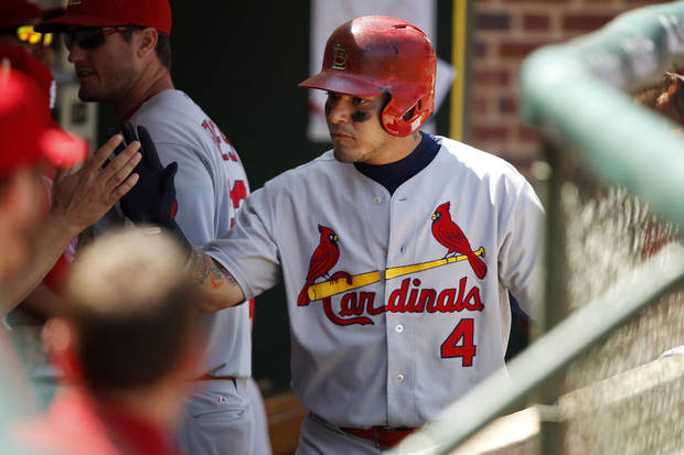 St. Louis Cardinals' Yadier Molina celebrates with teammates in the dugout after scoring on a hit by Jon Jay against the Chicago Cubs during the second inning of a baseball game on Sunday, Aug. 18, 2013, in Chicago. (AP Photo/Andrew A. Nelles)