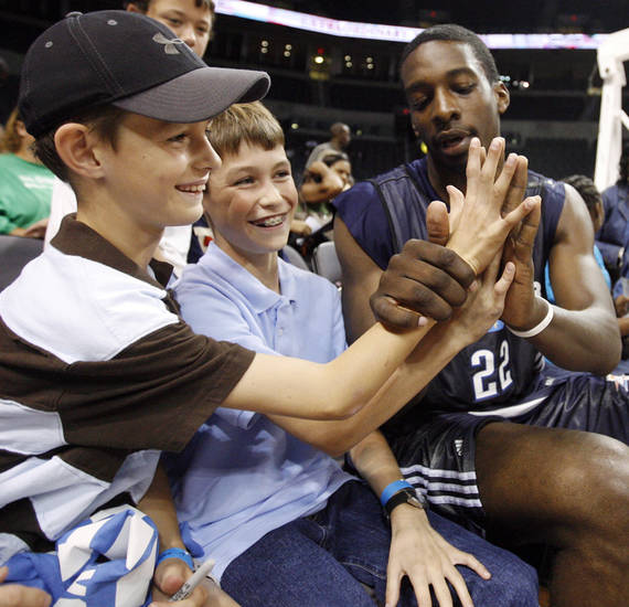 Oklahoma City's Jeff Green, right, checks the size of his hand against the hands of brothers Jeff Lee, 9, left, and Coley Lee, 12, during the open practice for the Oklahoma City Thunder NBA basketball team at the Ford Center in Oklahoma City, Monday, October 20, 2008. BY NATE BILLINGS, THE OKLAHOMAN
