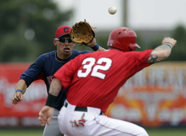 Los Angeles Angels' Josh Hamilton, right, gets caught in a rundown by Cleveland Indians shortstop Asdrubal Cabrera trying to steal third during the second inning of a spring training baseball game in Tempe, Ariz. Wednesday, March 20, 2013. (AP Photo/Chris Carlson)
