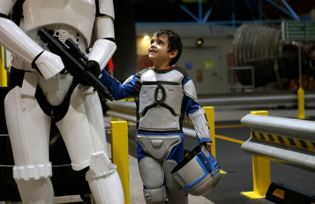 Michael Elden, 5, of Blanchard, looks up at his father, Mark Elden, as they get their photo taken during Science Museum Oklahoma�s Bright Night of Star Wars sleepover. Photos by Bryan Terry, The Oklahoman