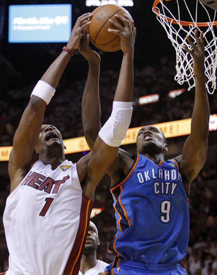 Oklahoma City's Serge Ibaka (9) goes for the ball beside Miami's Chris Bosh (1) during Game 3 of the NBA Finals between the Oklahoma City Thunder and the Miami Heat at American Airlines Arena, Sunday, June 17, 2012. Photo by Bryan Terry, The Oklahoman