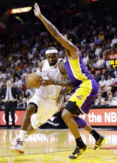 Miami Heat forward LeBron James, left, drives to the basket past Los Angeles Lakers forward Earl Clark during the first half of an NBA basketball game, Sunday, Feb. 10, 2013, in Miami. (AP Photo/Wilfredo Lee)