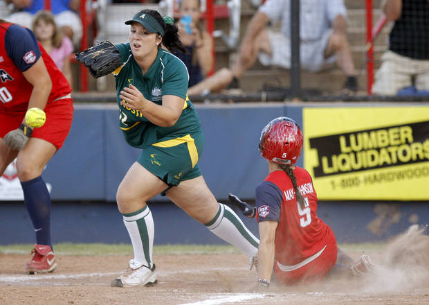 USA's Stacy May-Johnson scores past Australia's Kaia Parnaby in the fifth inning of a World Cup of Softball game between Team USA and Australia at ASA Hall of Fame Stadium in Oklahoma City, Friday, June 29, 2012. Photo by Bryan Terry, The Oklahoman