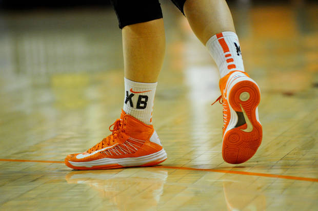 Oklahoma State sophomore guard Liz Donohoe&#039;s shoes are taped with the letters KB and MS to honor Kurt Budke and Miranda Serna, the two coaches killed in a plane crash one year ago on November 17, 2011. KT King/For the Tulsa World