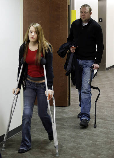Two people using crutches and a cane arrive for a court proceeding for Aurora theater shooting suspect James Holmes at the courthouse in Centennial, Colo., on Friday, Jan. 11,  2013. The judge granted a defense motion to delay the arraignment of Holmes until March 12. The decision comes a day after the judge ruled that Holmes should stand trial.  (AP Photo/Ed Andrieski)