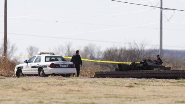 Investigators work on a crime scene in the death of Rosalin Reynolds, 8, on Wednesday in a field behind the Watonga apartment complex where she lived. <strong>Steve Gooch - The Oklahoman</strong>