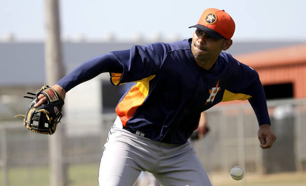 Houston Astros infielder Carlos Pena loses the ball as he tries to throw to third base during a spring training baseball workout Saturday, Feb. 16, 2013, in Kissimmee, Fla. (AP Photo/David J. Phillip)