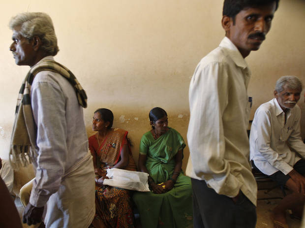In this Dec.10, 2012 photo, people wait to get their land registered at the government registrar&#039;s office in Hoskote 30 kilometers (19 miles) from Bangalore in the southern Indian state of Karnataka. For years, Karnataka&#039;s land records were a quagmire of disputed, forged documents maintained by thousands of tyrannical bureaucrats who demanded bribes to do their jobs. In 2002, there were hopes that this was about to change. (AP Photo/Aijaz Rahi)