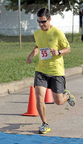 Mark Brown is the first runner to cross the finish at a 5K Run sponsored by the Cleveland County sheriff's office to raise money for Bridges on Saturday, June 9, 2012, in Norman, Okla.     Photo by Steve Sisney, The Oklahoman