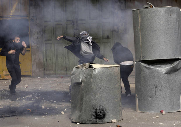 Palestinians throw stones during clashes with Israeli troops in the West Bank city of Hebron, following the death of Arafat Jaradat, a Palestinian prisoner held in an Israeli jail, Sunday, Feb. 24, 2013. The death of a 30-year-old Palestinian after interrogation by Israel's Shin Bet security service stokes new West Bank clashes, along with Israeli fears of a third Palestinian uprising. (AP Photo/Nasser Shiyoukhi)
