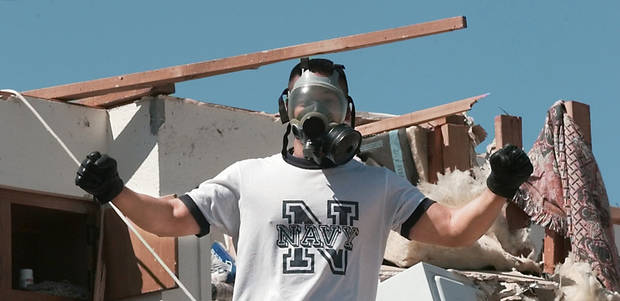 MAY 3, 1999 TORNADO: Tornado victims, damage: Navy ensign Bernard Calamug, stationed at Tinker Air Force Base, located his navy issued gas mask while searching through debris for personal items in his second floor apartment at the Emerald Spring Apartments across from West Moore High School, 12500 S Western.