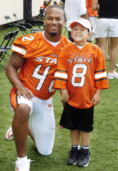 STILLWATER, OK; TUESDAY, AUGUST 10, 2004; OSU media/fan apreciation day.   Tyler Kevin Norris, 6, from Stillwater, has a photo made with defensive lineman Trumain Carroll on the field.  Staff Photo by Steve Sisney