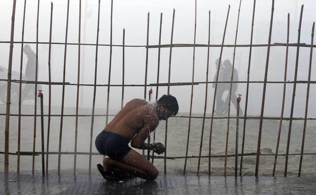An Indian man bathes under a tap on the banks of the Ganges River on a cold and foggy morning in Allahabad, India, Sunday, Dec. 30, 2012. North India continues to face extreme weather conditions with dense fog affecting flights and trains. (AP Photo/Rajesh Kumar Singh)