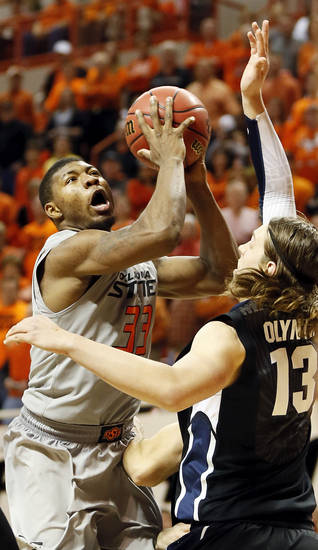 Oklahoma State's Marcus Smart (33) attacks the basket as Gonzaga's Kelly Olynyk (13) defends during a men's college basketball game between Oklahoma State University (OSU) and Gonzaga at Gallagher-Iba Arena in Stillwater, Okla., Monday, Dec. 31, 2012. Gonzaga won, 69-68. Photo by Nate Billings, The Oklahoman