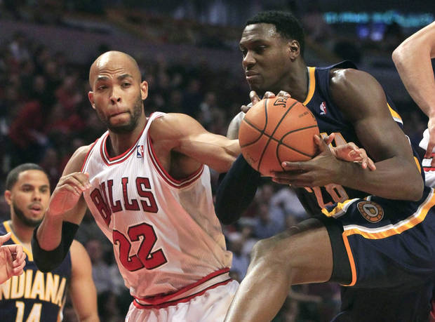 Chicago Bulls forward Taj Gibson (22) fouls Indiana Pacers center Ian Mahinmi during the first half of an NBA basketball game Tuesday, Dec. 4, 2012, in Chicago. (AP Photo/Charles Rex Arbogast)