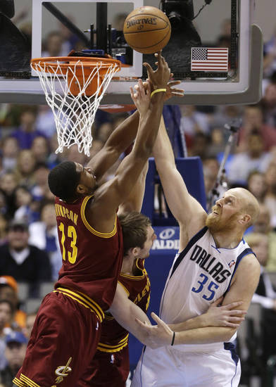 Dallas Mavericks center Chris Kaman (35) has his shot defended by Cleveland Cavaliers Tristan Thompson (13) and Luke Walton (4) during the first half of an NBA basketball game Friday, March 15, 2013, in Dallas. (AP Photo/LM Otero)