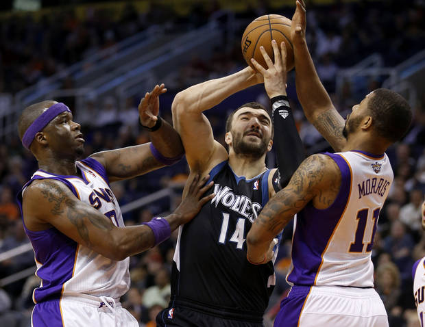 Minnesota Timberwolves' Nikola Pekovic (14), of Montenegro, drives between Phoenix Suns' Markieff Morris (11) and Jermaine O'Neal during the first half of an NBA basketball game, Tuesday, Feb. 26, 2013, in Phoenix. (AP Photo/Matt York)