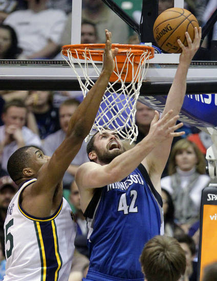 Minnesota Timberwolves power forward Kevin Love (42) lays the ball up as Utah Jazz power forward Derrick Favors (15) defends in the third quarter during an NBA basketball game on Wednesday, Jan. 2, 2013, in Salt Lake City.   (AP Photo/Rick Bowmer)