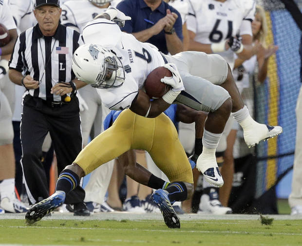 Nevada running back Don Jackson, top, flips over UCLA cornerback Fabian Moreau during the first half of an NCAA college football game in Pasadena, Calif., Saturday, Aug. 31, 2013. (AP Photo/Chris Carlson)