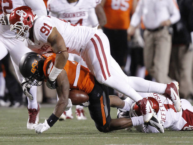 Oklahoma's R.J. Washington (91) brings down Oklahoma State's Joseph Randle (1) during the Bedlam college football game between the Oklahoma State University Cowboys (OSU) and the University of Oklahoma Sooners (OU) at Boone Pickens Stadium in Stillwater, Okla., Saturday, Dec. 3, 2011. Photo by Chris Landsberger, The Oklahoman