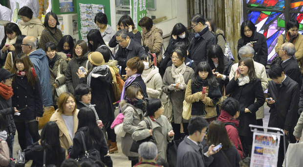 People use mobile phones as they are stranded at Sendai railway station in Sendai, Miyagi Prefecture, Friday, Dec. 7, 2012 after trains were halted following a strong earthquake that struck off the coast of northeastern Japan. It is the same region that was hit by a massive earthquake and tsunami last year. (AP Photo/Kyodo News) JAPAN OUT, MANDATORY CREDIT, NO LICENSING IN CHINA, FRANCE, HONG KONG, JAPAN AND SOUTH KOREA