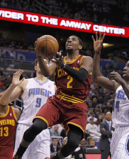 Orlando Magic center Nikola Vucevic (9) and Andrew Nicholson (44) can't stop Cleveland Cavaliers guard Kyrie Irving (2) who  lays the ball up during the first half of an NBA basketball game against the Orlando Magic in Orlando, Fla., on Saturday, Feb. 23, 2013. (AP Photo/Reinhold Matay)