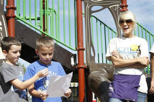 Carrie Underwood, right, reacts to Second graders Kayson Flud and Rylee Campbell reading a letter of appreciation for helping build a playground at her former school, Marshall Elementary School, in Checotah, Friday, October 14, 2011. Photo by David McDaniel, The Oklahoman  ORG XMIT: KOD