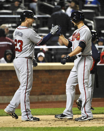 Atlanta Braves' Chris Johnson (23) congratulates teammate Mike Minor at home plate after Minor hit a two-run home run off New York Mets starting pitcher Dillon Gee in the fifth inning of the second baseball game at Citi Field on Saturday, May 25, 2013, in New York. (AP Photo/Kathy Kmonicek)