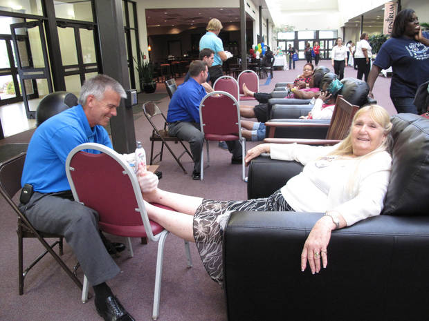 "United Methodist Church of the Servant volunteer Tom Pace massages the feet of a ""Queen For A Day"" participant at the recent event sponsored by the Oklahoma City-based Single Parent Support Network at the church, 14343 N MacArthur. Photo by Carla Hinton, The Oklahoman <strong></strong>"