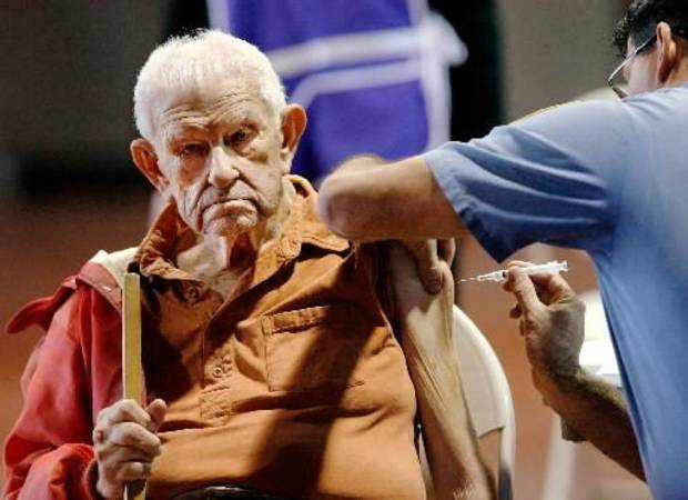Lawrence Hon, 96, of  Oklahoma City receives an injection of H1N1 vaccine from  Oklahoma City Fire Department Lt. Jason Martinez in the Centennial Building at State Fair Park Tuesday morning, Nov. 24, 2009. Photo by Jim Beckel